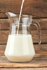 Milk pouring into a jug. Filling a glass pitcher with fresh milk. Eco milk concept.
