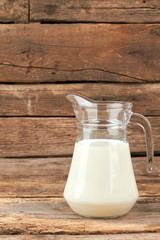 Organic milk in glass jug. Natural cow milk in glass pitcher on rustic wooden boards. Health benefits of milk.