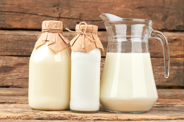 Organic cow milk in glass dishes. Vintage style bottles with milk and sour cream. Natural milk for health.