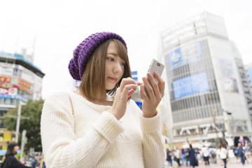 女性・スマホを操作・渋谷スクランブル交差点