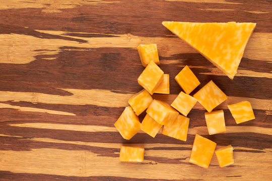 Cubes of marble cheese on wooden background. Marble cheese on textured wood. Delicious dairy product.