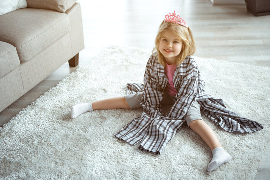 Playful kid is having fun at home. Little princess is wearing large clothing of her daddy while sitting on floor. She is looking at camera and laughing