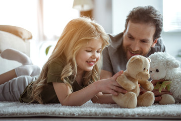 Cute blonde girl is playing with teddy bear with excitement. She is lying on carpet in room. Father is looking at kid with love and smiling