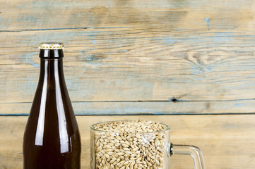 Glass and bottle of beer, ears of barley on wooden background. Ale. horizontal with copy space