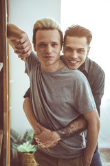 Waist up portrait of handsome guy with dyed hair leaning against wooden wall unit while his boyfriend embracing him from behind. Guys posing at home