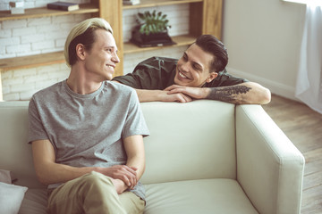 Are you flirting with me. Toned portrait of blond young man sitting on couch while his cheerful boyfriend standing behind and gazing at him