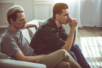 Toned side view portrait of gay couple having problems in relationship. They looking away with unhappy expressions