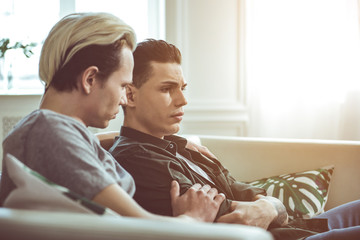Something wrong. Toned side view portrait of unhappy gay couple sitting on couch at home