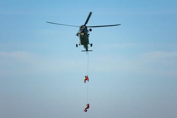 Rescue helicopter and rescuer on the rope - life-saving flying vehicle and blue sky (muted contrast)