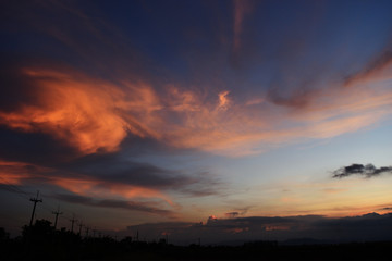 Silhouette  of electricity poles and tree at the roadside with beautiful blue sky at sunset, The horizon began to turn orange with purple and pink cloud at night, Dramatic cloudscape area