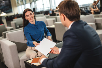 Cheerful business lady taking papers, reached by man sitting afore her. She looking at him with bright smile