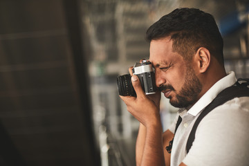 Close up of a pleasant Hindu man enjoying his hobby while making photos