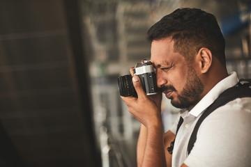 Close up of a pleasant Hindu man enjoying his hobby while making photos
