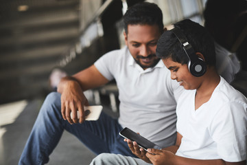Joyful delighted little boy wearing headset while testing his modern smartphone with his father