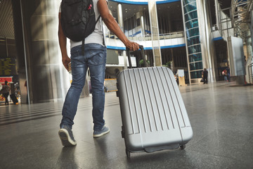 Low angle of a plastic silver luggage carried by a man who is hurrying up not to miss his flight