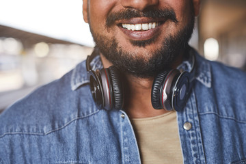 Close up of a joying bearded hindu man smiling while being a music lover