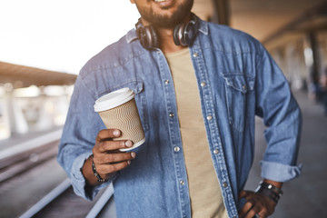 Close up of a coffee cup being used by a cheerful hindu man who is standing on the railway platform