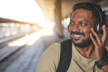 Joyful adult hindu man enjoying music while waiting for a train on the platform