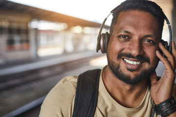 Close up of a bearded positive hindu man wearing headphones while expressing joy