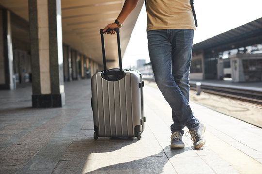 Lets start the journey. Low angle of a pleasant man standing on the platform and holding his luggage