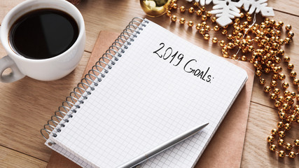 2019 goals list in notebook, cup of coffee on wooden desk