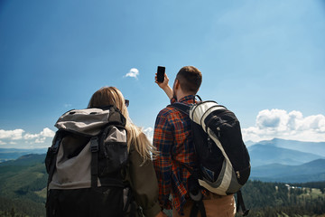 Man and woman hiking together with rucksacks in highland. They standing on top with focus on back and guy is lifting arm with smartphone for taking joint picture