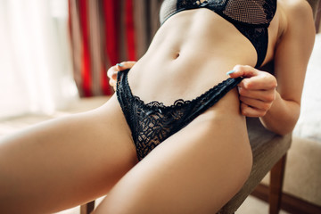 Naked lady in black underwear poses on a chair
