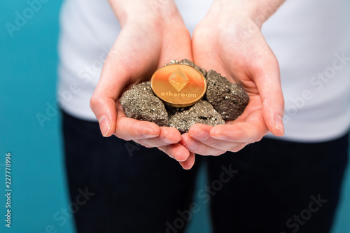 Young woman with a gold ethereum with raw gold nuggets on a