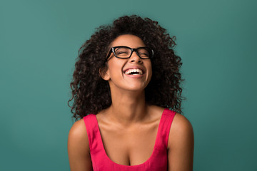 Happy african-american woman laughing over blue background