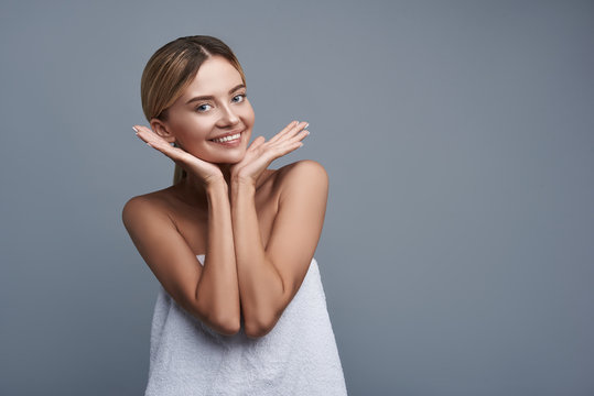 Pleased young lady feeling satisfied with the condition of her skin and smiling while standing in white towel