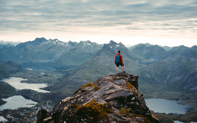 Adventurous man is standing on top of the mountain and enjoying the beautiful view during a vibrant sunset. Beautiful Nature Norway natural landscape aerial photography Wall mural