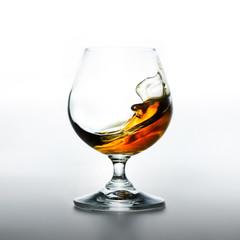 Cognac glass with splashing brandy inside