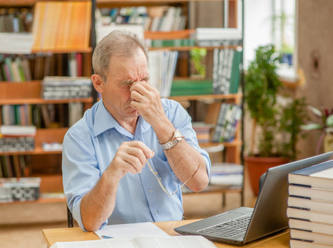 Tired senior man having a headache in library after using the computer