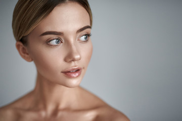 Interest. Young fair haired lady with clean skin having laconic make up and looking into the distance while standing alone