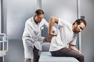Medical adviser carefully inspecting back of young man and looking for center of pain