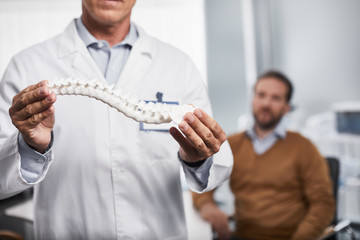 Close up of medical adviser explaining for male patient and showing how spine looking