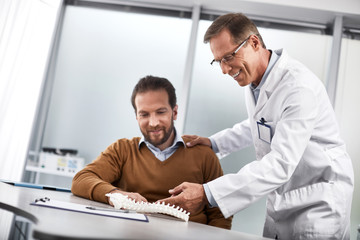 Waist up portrait of smiling doctor in glasses showing for male patient plastic model of spine and explaining treatment principle