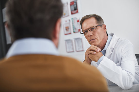 Doctor carefully listening his patient in cabinet. He trying to understand what worry about man