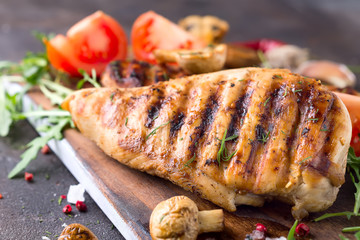 Grilled chicken fillets on wooden board on Gray concrete background. Healthy diet food concept, close up