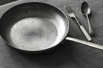 Rustic Frying Pan and Cutlery on the Top of Kitchen Table