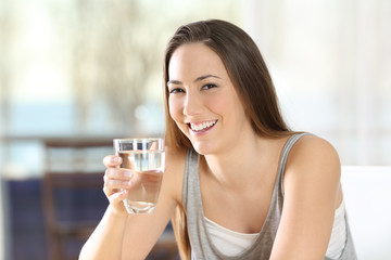 Happy woman posing holding a glass of water
