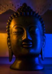 Black bust sculpture Buddha illuminated in blue and orange
