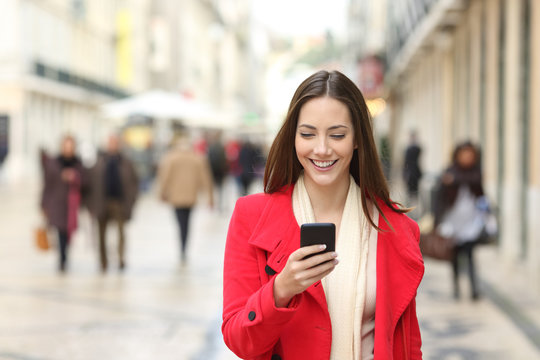 Happy woman walking using a cellphone in the street