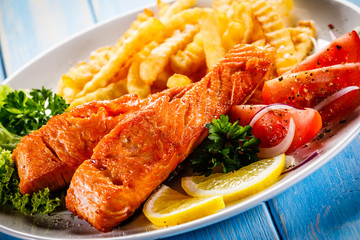 Fried salmon, French fries and vegetables