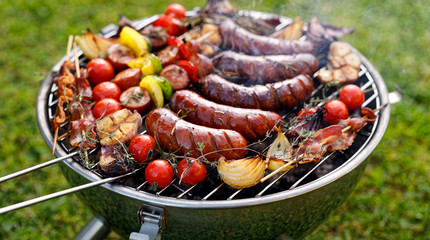 Acrylic Prints Grill / Barbecue Grilled food. Various grilled products: Grilled sausages, meat and vegetable skewers, bacon and vegetables on the grill plate, outside. Barbecue, bbq