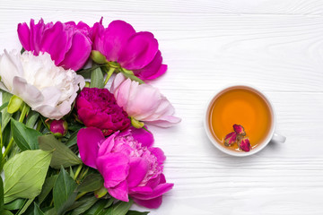 A cup of tea and peonies flowers on a white wooden background. Mockup for your design. View from above.