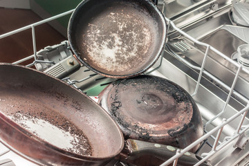 Dirty pans lie in the dishwasher for washing