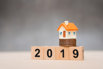 Miniature house on  stack coins and year 2019 wooden block using as business and property concept