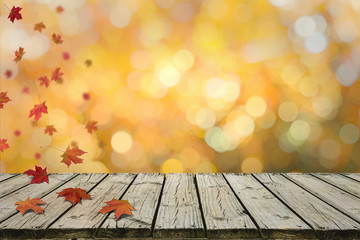 Autumn Maple leaves falling on rustic wooden deck with nice bokeh in autumn tone in background. For display or montage your products.