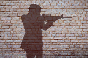 Schatten von einem Mann mit automatischer Waffe vor einer Wand aus Ziegelsteinen
